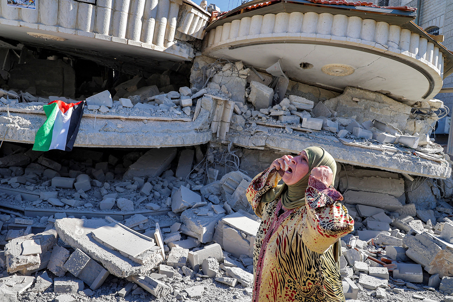 Woman cries near demolished building in West Bank