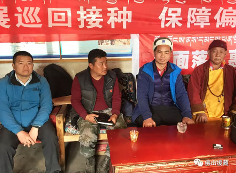 """Xie Guogao (third from left), a Chinese official from Guangdong, during the third """"relocation for poverty alleviation mobilization"""" visit by his team to Doka village, Metog, in southeastern Tibet. Xie is delivering a public lecture to village elder Ding X (right) about the benefits of relocating to a border village in a video from Jan. 24, 2019. The Tibetan translator is seated to Xie's left."""