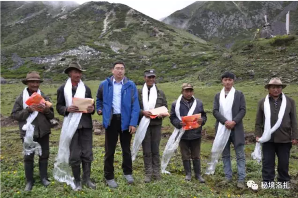 """Zhao Tianwu (third from left), the party secretary of Lhodrak county, poses for the camera after presenting scarves and gifts of cash to the herders in the Beyul on July 7, 2017, in an image posted to WeChat. <span class=""""attribution"""">Hidden Lhodrak, WeChat channel of the Lhodrak County Party Committee Office via the Lhodrak County Party Committee Office</span>"""