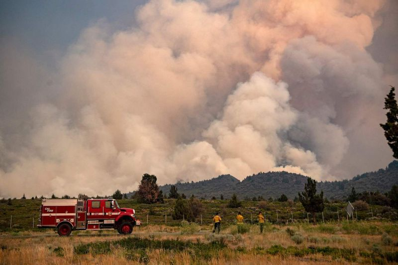 Firefighters monitor a wildfire in California