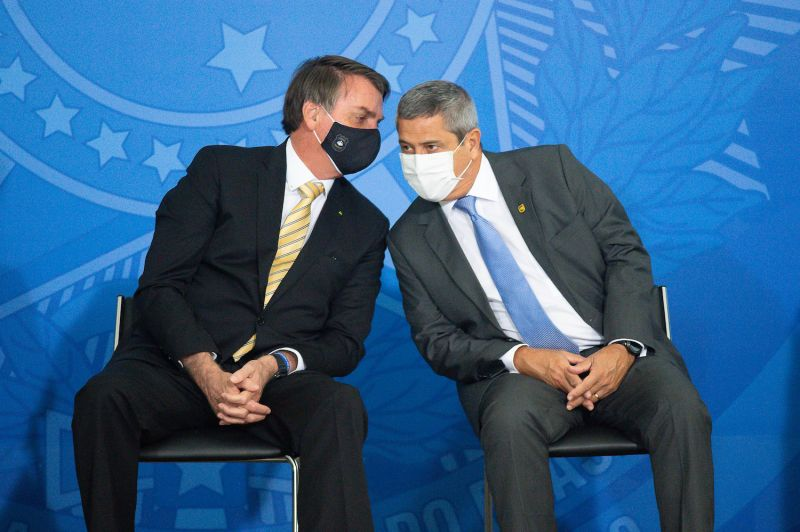 Brazilian President Jair Bolsonaro and Brazilian Chief of Staff General Braga Netto talk during the launch of a new campaign against domestic violence during the coronavirus pandemic at the Planalto Palace in Brasilia on May 15, 2020.
