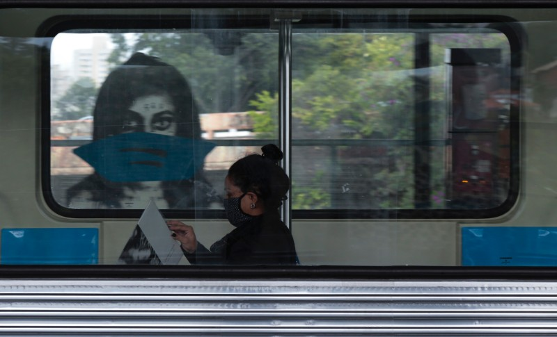 A woman wearing a face mask reads inside a subway in São Paulo on May 7, 2020.