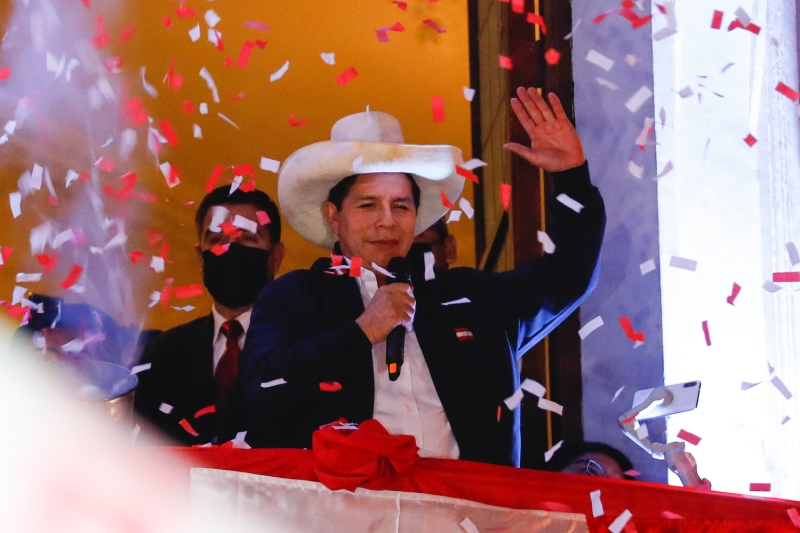 Peruvian President-elect Pedro Castillo waves at supporters after being confirmed as the winner of Peru's June 6 presidential runoff election at his campaign headquarters in Lima on July 19.