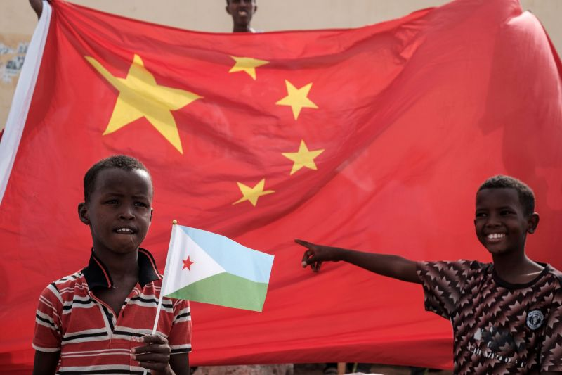 A boy holds a Djiboutian national flag in front of a Chinese national flag at the launching ceremony of new housing construction project in Djibouti on July 4, 2018.