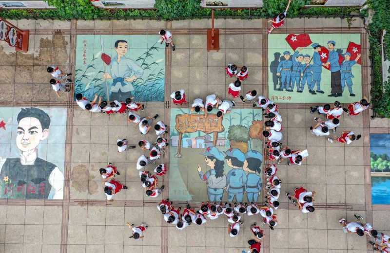 Students draw images commemorating the 100th anniversary of the Chinese Communist Party in Qingzhou, China, on June 24.