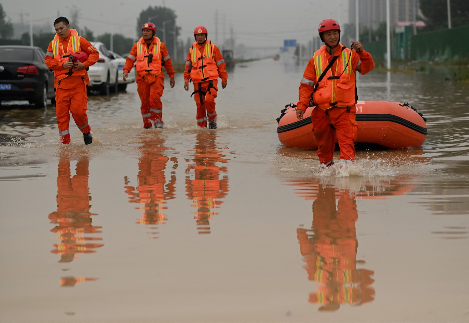 Rescue workers cross a flooded street following heavy rain that claimed the lives of at least 33 people in Zhengzhou, China, on July 23.