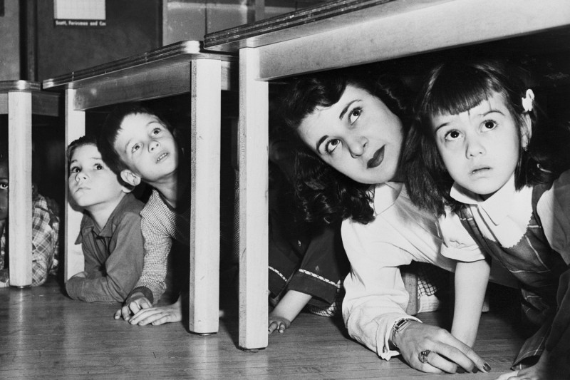 Schoolchildren and their teacher peer out from under their desks during a Cold War air raid drill