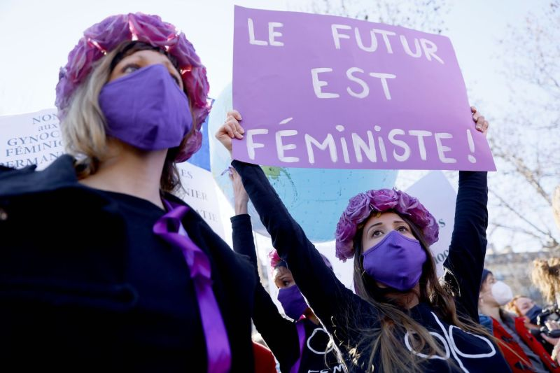 """A Femen protester holds a placard reading """"The Future is Feminist"""" at a demonstration in Paris on March 7."""