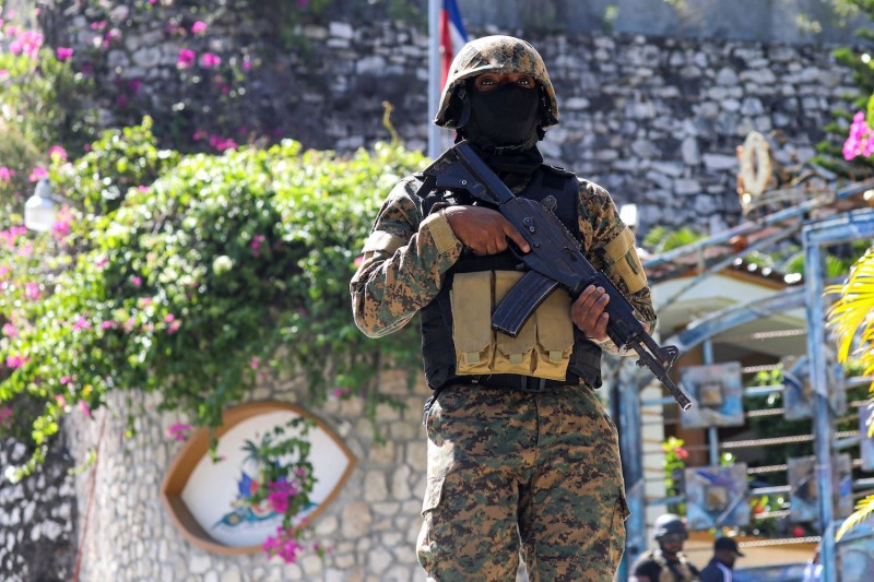 A Haitian police officer stands guard.