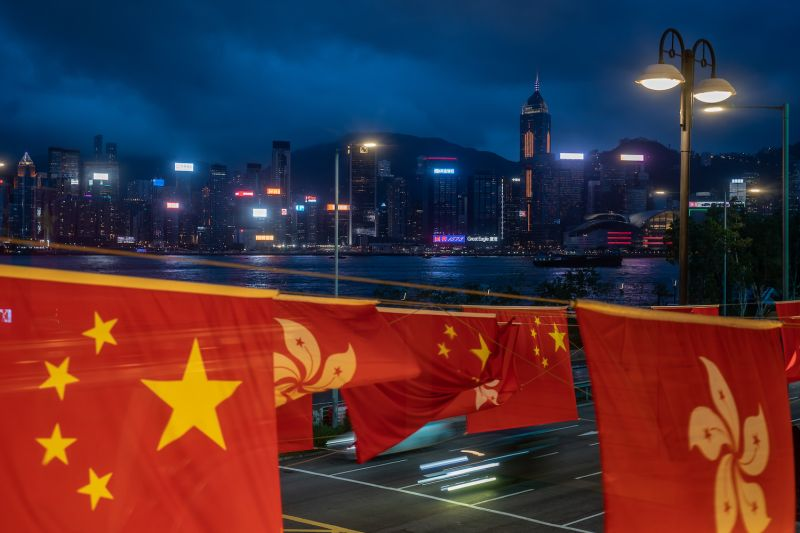 The flags of China and Hong Kong against the city's skyline in Hong Kong.