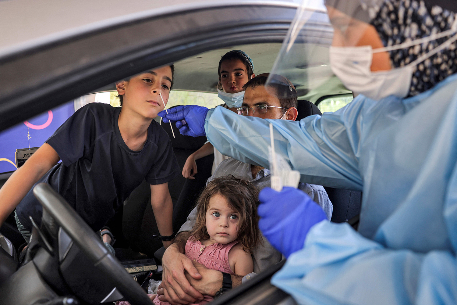 A medic performs coronavirus swab test on a child in a vehicle at a Home Front command drive-through testing complex in Jerusalem on July 29.