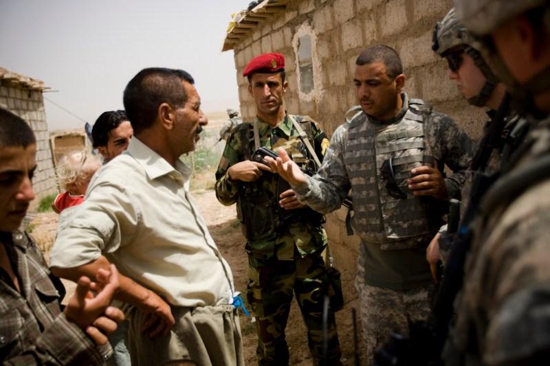 An interpreter speaks with Kurdish villagers.