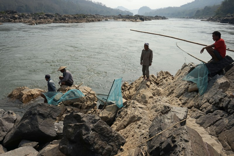 Fishermen lay their nets on the Mekong River close to the site of an approved dam site near Luang Prabang, Laos, on Feb. 8 2020.