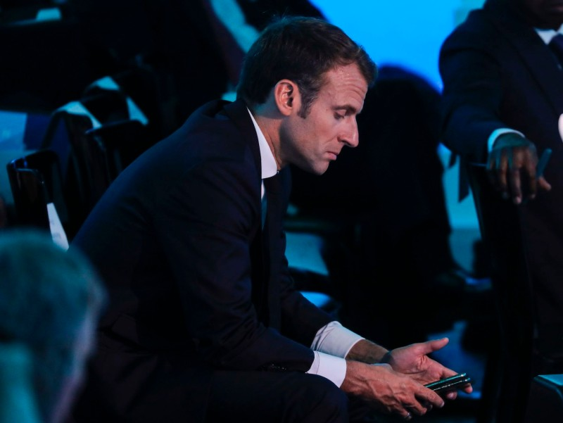 The French president looks at his phone during a U.N. meeting.