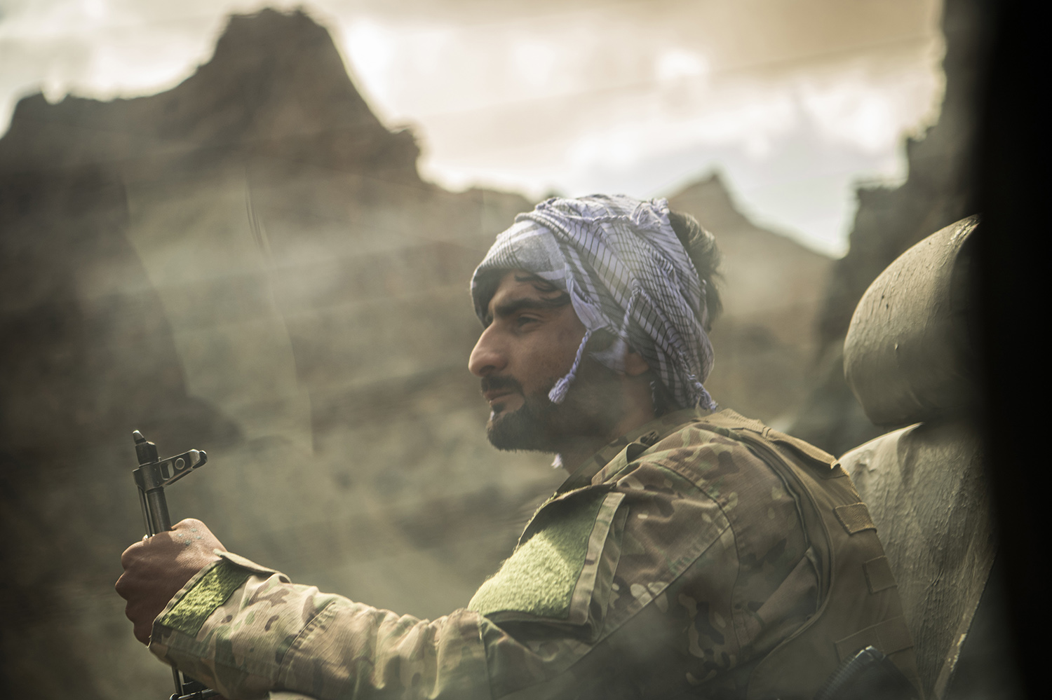 A soldier sits at the back of a police vehicle on its way from Bamiyan city to Saighan district on July 21.