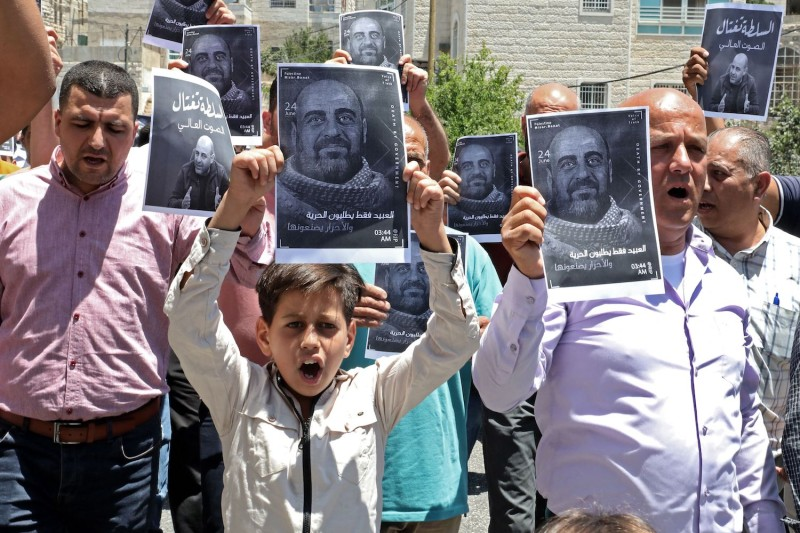 Demonstrators hold up images of late Palestinian activist Nizar Banat, who died in late June during a violent arrest by Palestinian Authority security forces, as they march during a protest in the city of Hebron in the occupied West Bank on July 2, 2021.