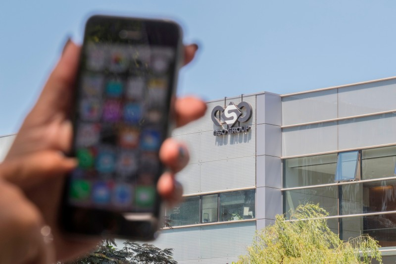 A woman displays her iPhone in front of the building housing the Israeli NSO Group in Herzliya, Israel, on Aug. 28, 2016.