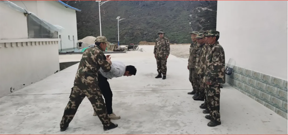 An anti-terrorist police officer from the Tibetan capital of Lhasa, stationed in Gyalaphug as a member of the village-resident cadre work team, demonstrates how to handle would-be escapees and illegal border crosserss to members of the village's Joint Defense Team on Dec. 16, 2020.