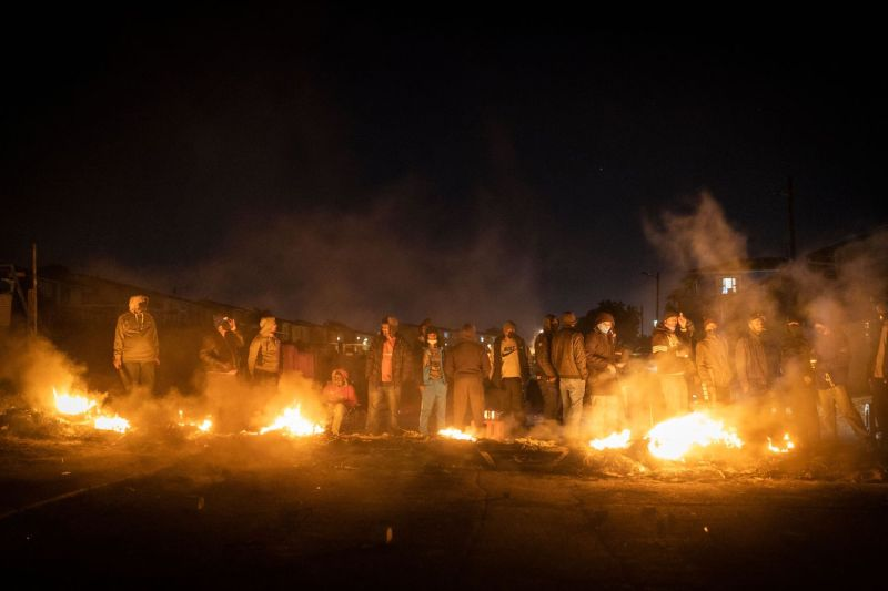 Armed people gather around a fire to keep warm at a road block set up to prevent looters from reaching the community in Phoenix Township, North Durban, South Africa, on July 15.