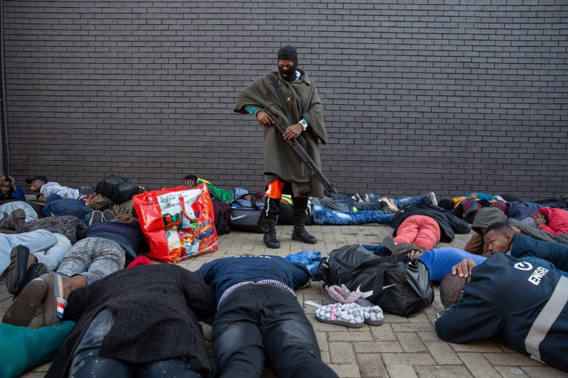 A police officer guards a group of suspected looters who were apprehended at a shopping center in Vosloorus, Johannesburg.