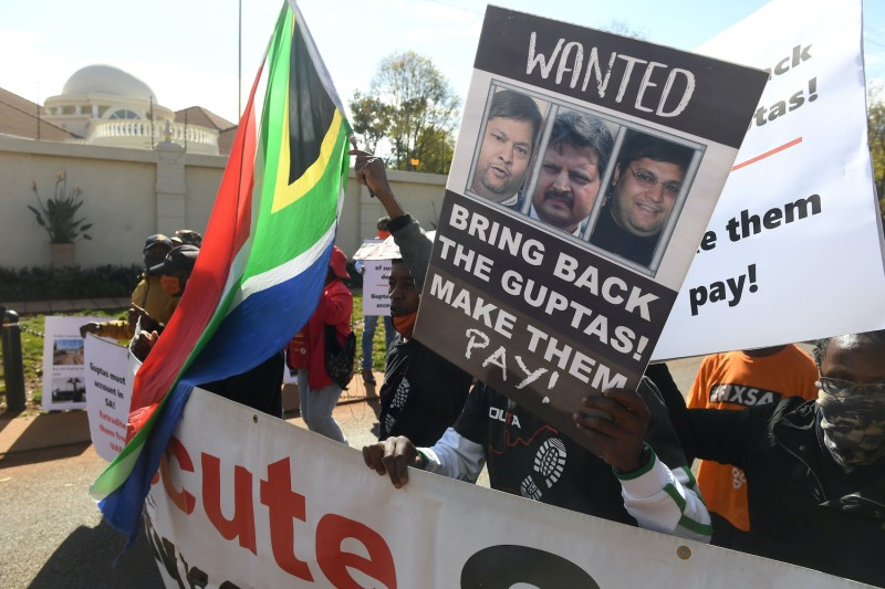 A group of people protest  outside the United Arab Emirates' embassy calling for the speedy extradition of the Guptas on June 10, in Pretoria, South Africa.
