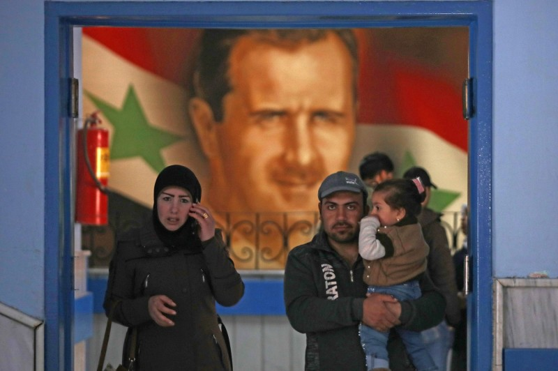A man, woman, and child in the doorway of a Syrian hospital