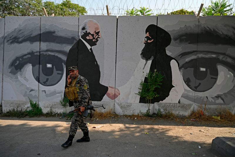A security officer walks past a mural showing U.S. Special Representative for Afghanistan Reconciliation Zalmay Khalilzad and Taliban co-founder Mullah Abdul Ghani Baradar, in Kabul on July 31, 2020.