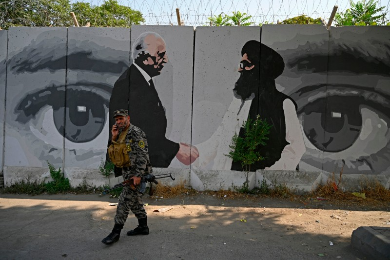 A security officer walks past a mural showing U.S. Special Representative for Afghanistan Reconciliation Zalmay Khalilzad and Taliban co-founder Mullah Abdul Ghani Baradar in Kabul on July 31, 2020.