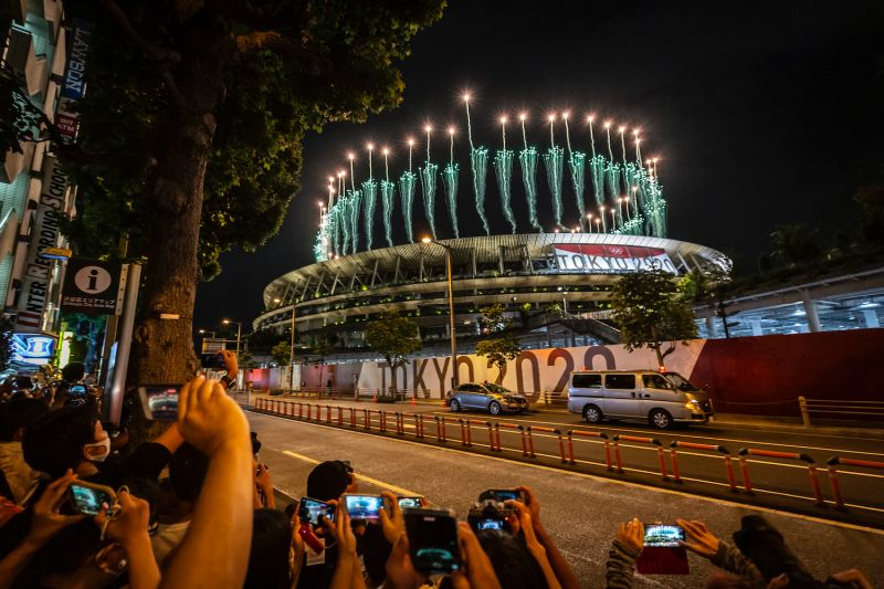 People take photographs of fireworks during the opening ceremony of the Tokyo Olympic Games at the Olympic Stadium in Tokyo on July 23.