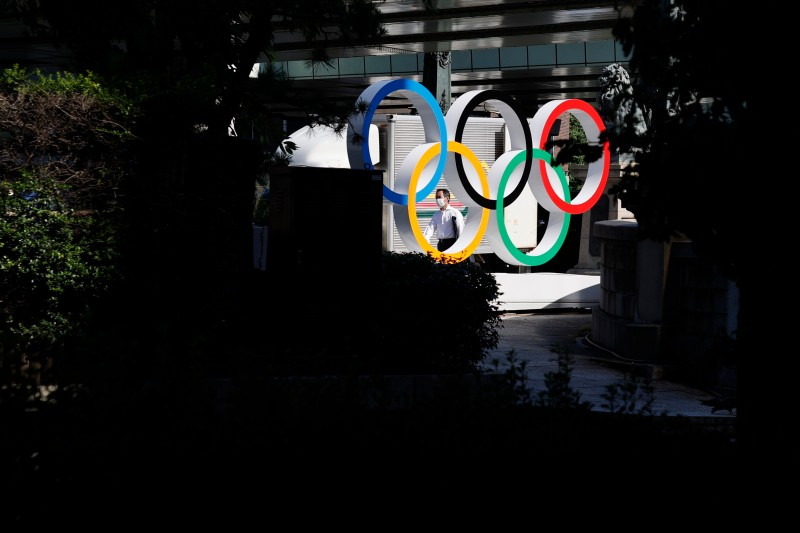 A man wearing a face mask walks past the Olympic Rings ahead of the Tokyo 2020 Olympic Games on July 19, 2021 in Tokyo, Japan.