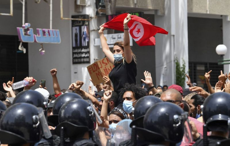 A protester lifts a Tunisian national flag during an anti-government rally in front of the parliament in Tunis, Tunisia.