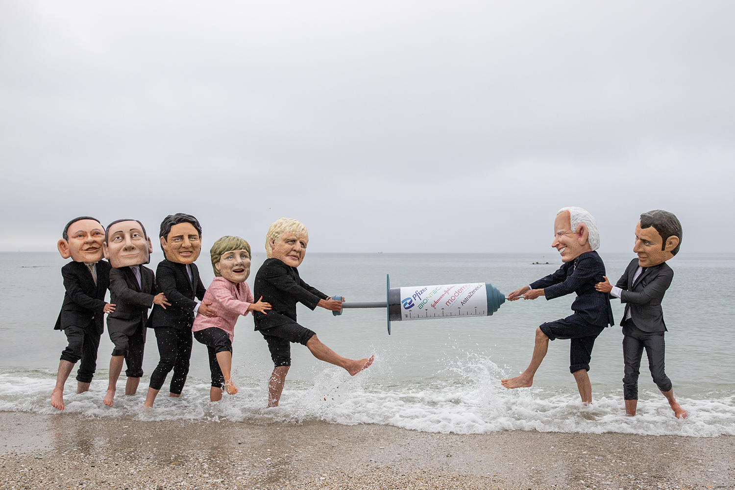People's Vaccine Alliance campaigners pose as G-7 leaders fighting over a COVID-19 vaccine in Falmouth, England, on June 11.