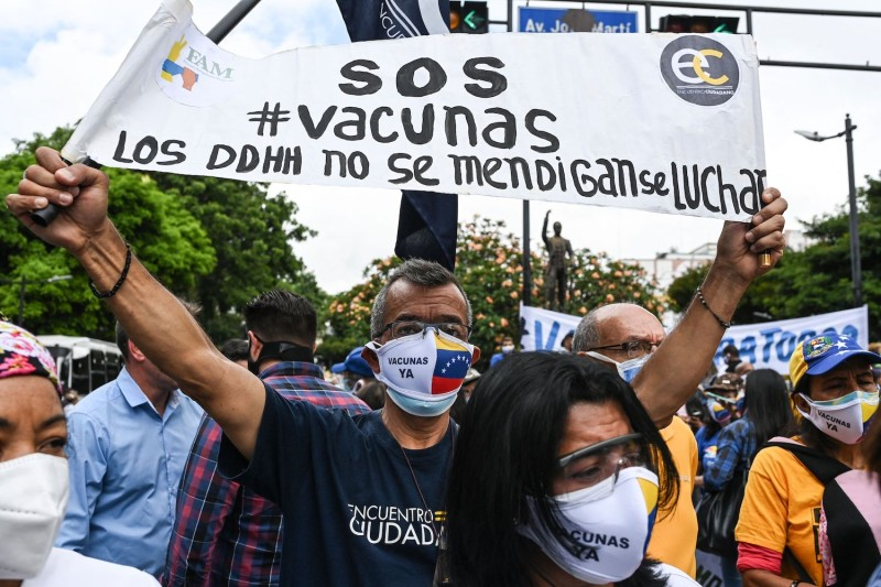 """An opposition activist holds a banner that reads """"vaccination now"""" during a protest to demand the government generally vaccinate the population in Caracas, Venezuela, on May 28."""