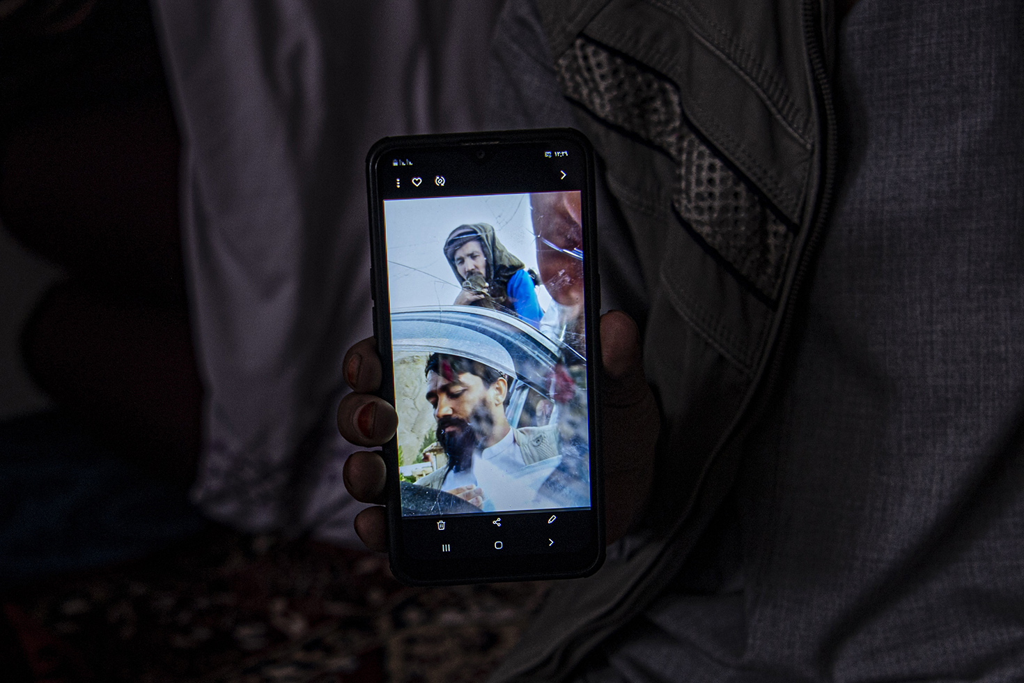 Sakhizada, shows a photo on his phone of a Taliban commander during an interview in Saighan district on July 21.