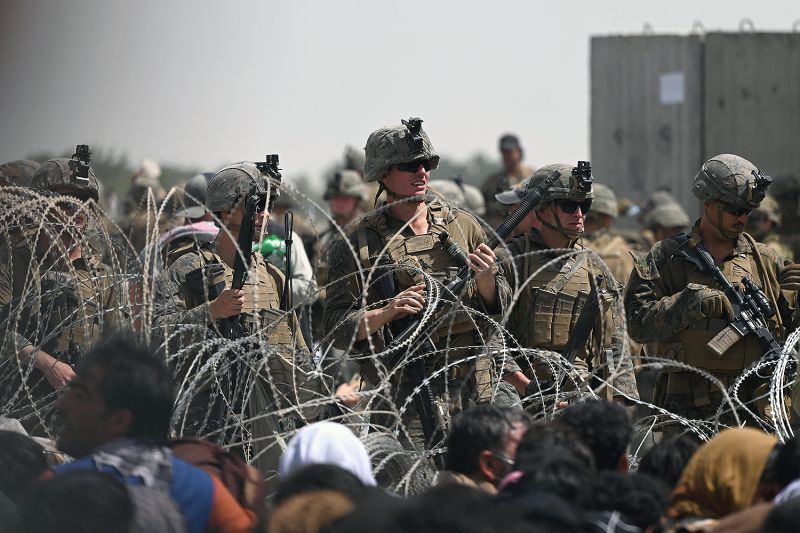 U.S. soldiers stand guard behind barbed wire