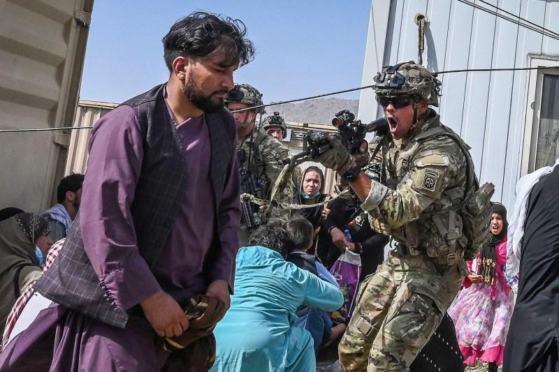 A U.S. soldier points his gun toward an Afghan passenger