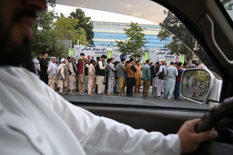 Afghans wait for the banks to open in Kabul.