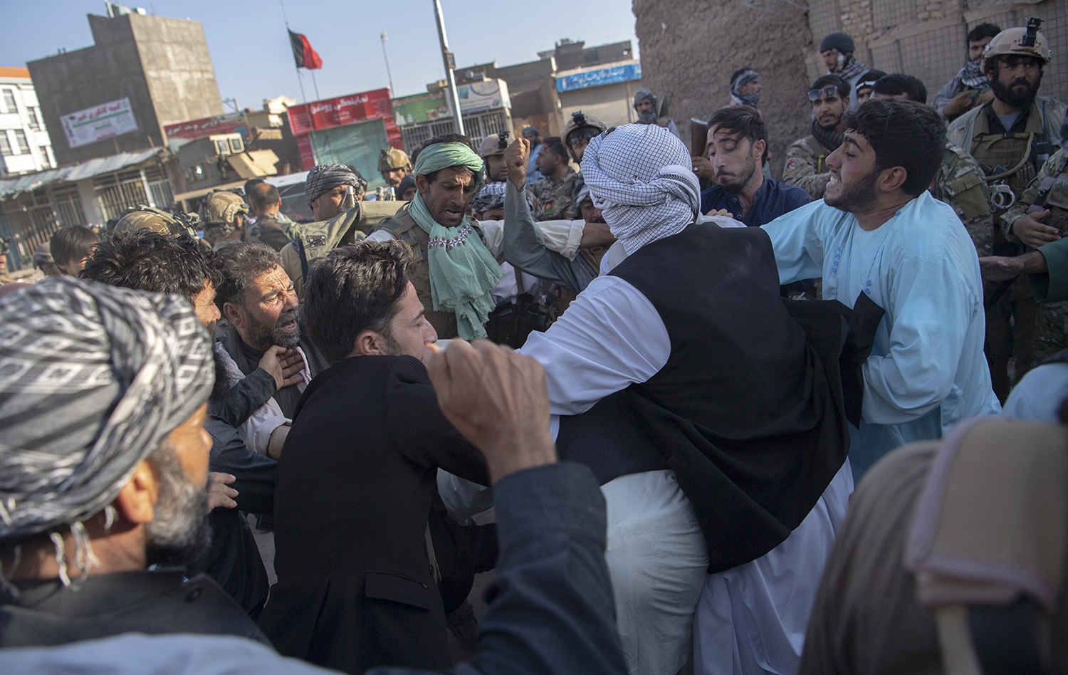 Militia members of Ismail Khan's forces beat an unseen man who they claim is a Taliban insurgent or sympathizer during a clash inside Herat city on Aug. 2.