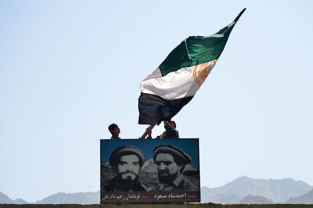 Afghan men wave a flag above the portrait of late Afghan commander Ahmad Shah Massoud.