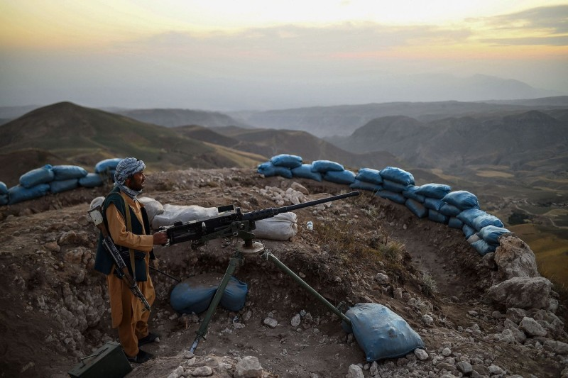 An Afghan militia fighter keeps watch at an outpost against Taliban insurgents.