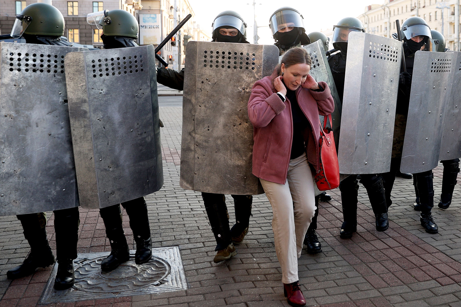 A woman is jostled by a wall of law enforcement officers as they block the road during a demonstration in Minsk on Sept. 20, 2020.
