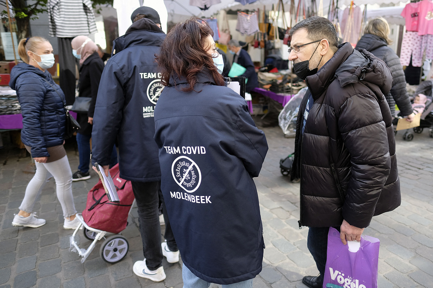 Members of a COVID-19 team talk to people in Brussels