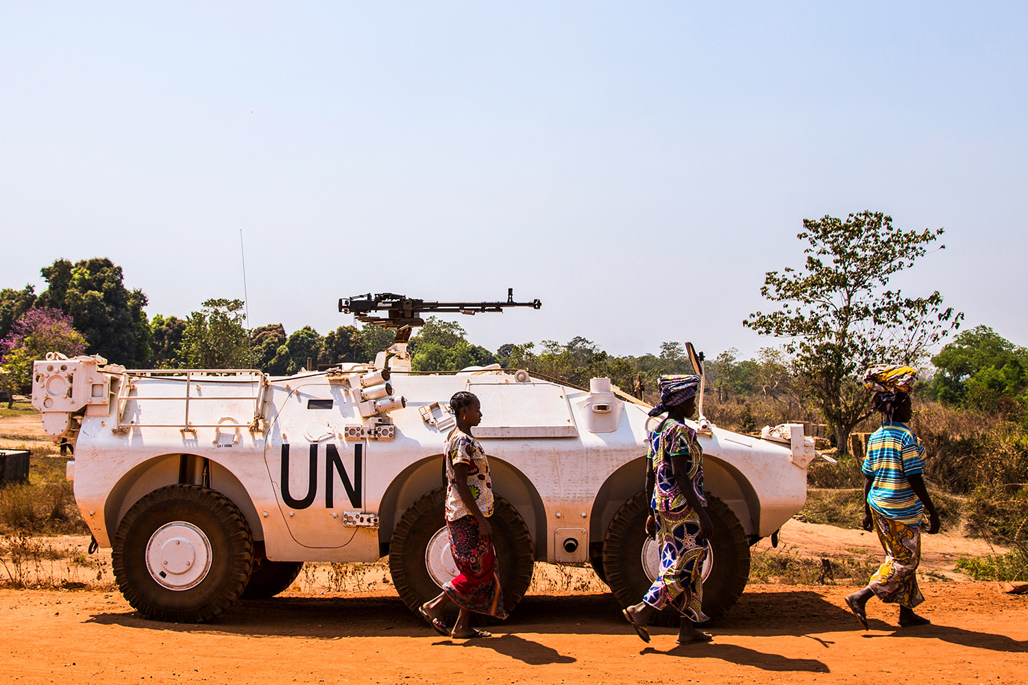 Women walk past a U.N.-armored personnel carrier