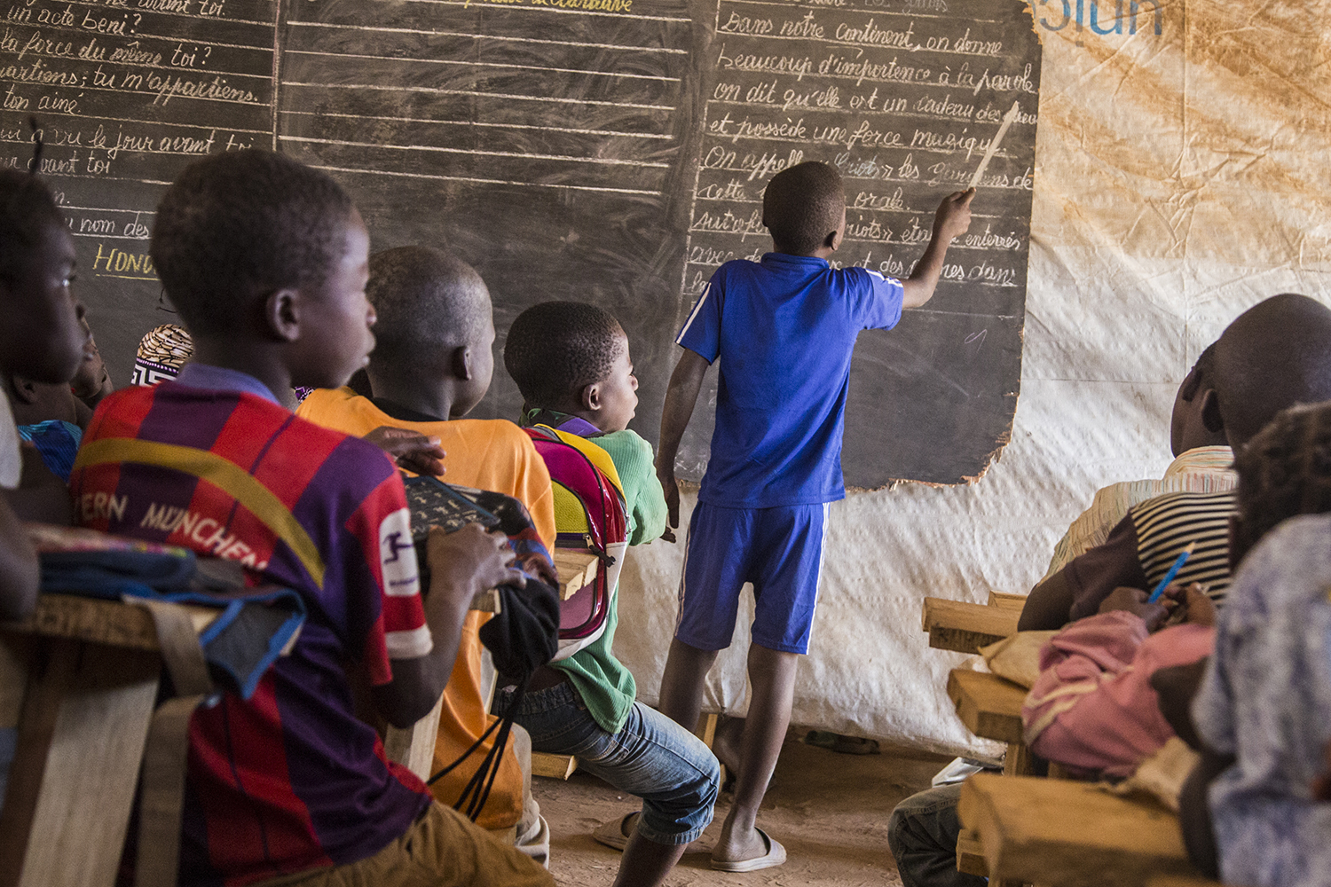 Children learn at a makeshift learning space at a sprawling displacement camp