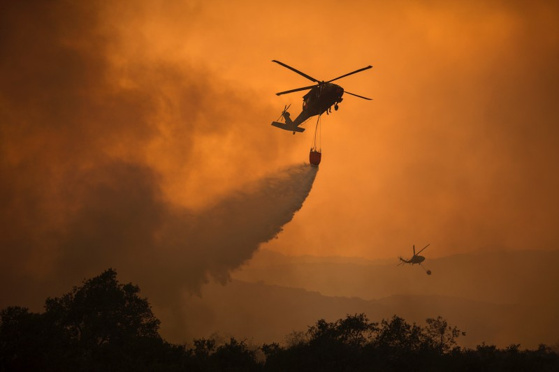 National Guard helicopters spray water as a wildfire approaches in California.