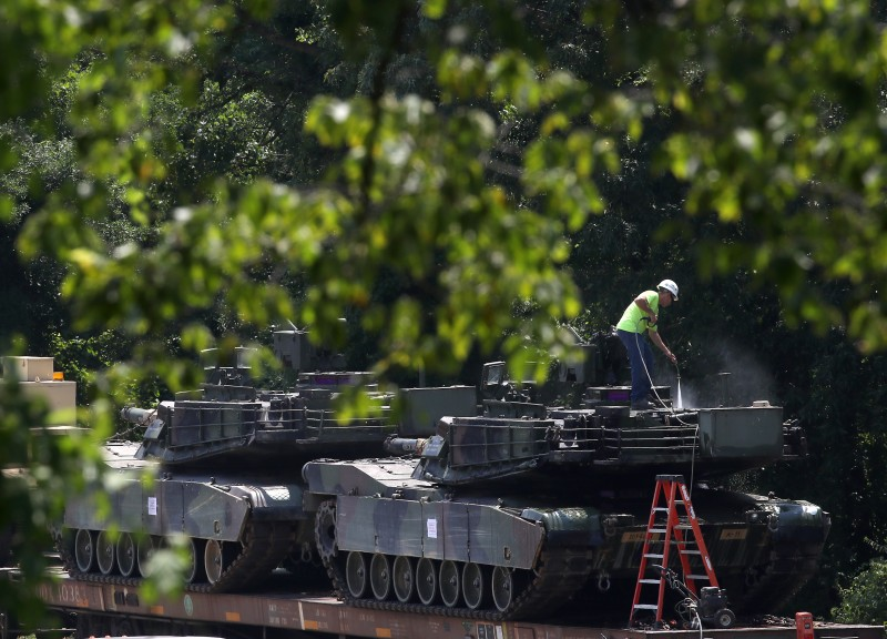 A worker washes one of two M1A1 Abrams tanks.