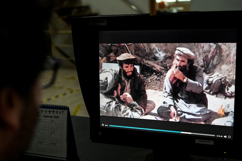 A man watches a new documentary tracing the life of Jalaluddin Haqqani, founder of the Haqqani network, a violent Taliban wing, on a monitor in Islamabad on Oct. 23, 2020.