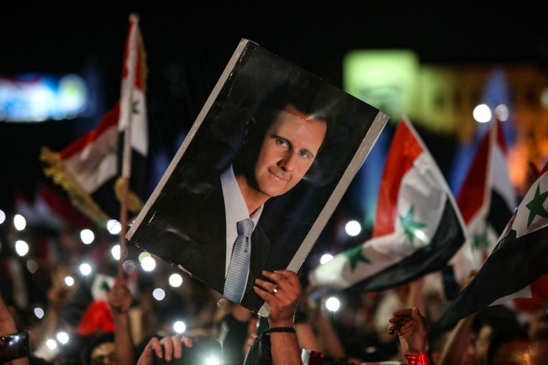 Syrians wave national flags and carry a portrait of Bashar al-Assad in Syria.
