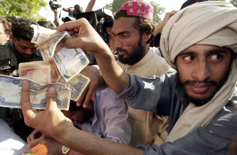 A demonstrator shows Pakistani currency notes contributed by the protestors for holy war against America and to help Afghanistan's ruling Taliban militia during an anti-US protest rally of a Sunni extremist group Sipah-i-Sahaba Pakistan (SSP) in Islamabad on September 28, 2001.