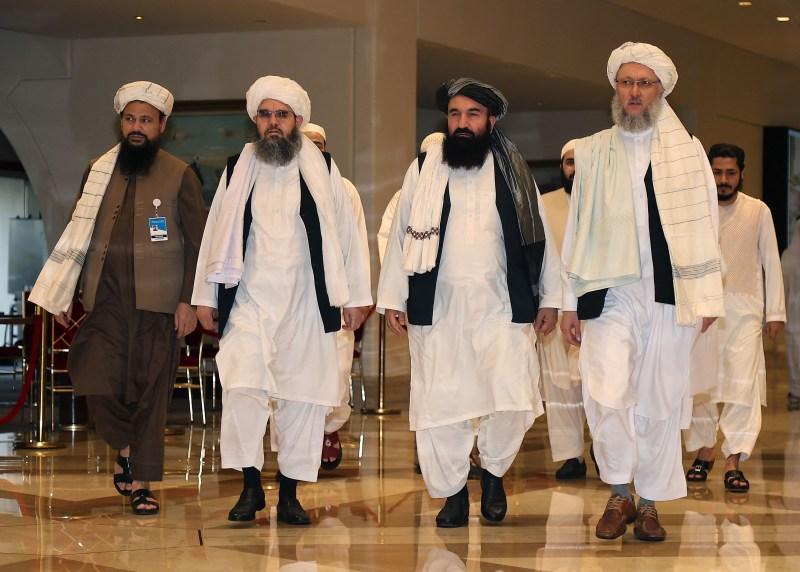 Head of the Taliban delegation Abdul Salam Hanafi, accompanied by Taliban officials Amir Khan Muttaqi, Shahabuddin Delawar and Abdul Latin Mansour, walks down a hotel lobby during the talks in Qatar's capital Doha on Aug. 12.